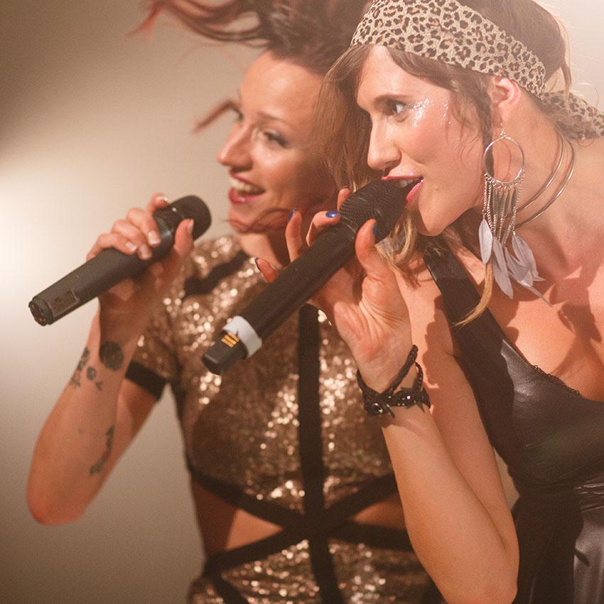 Female vocalists singing together.