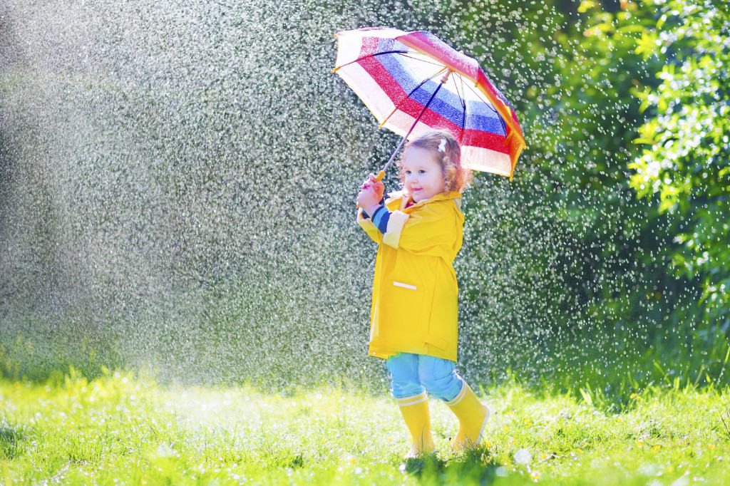 child in rain with umberella