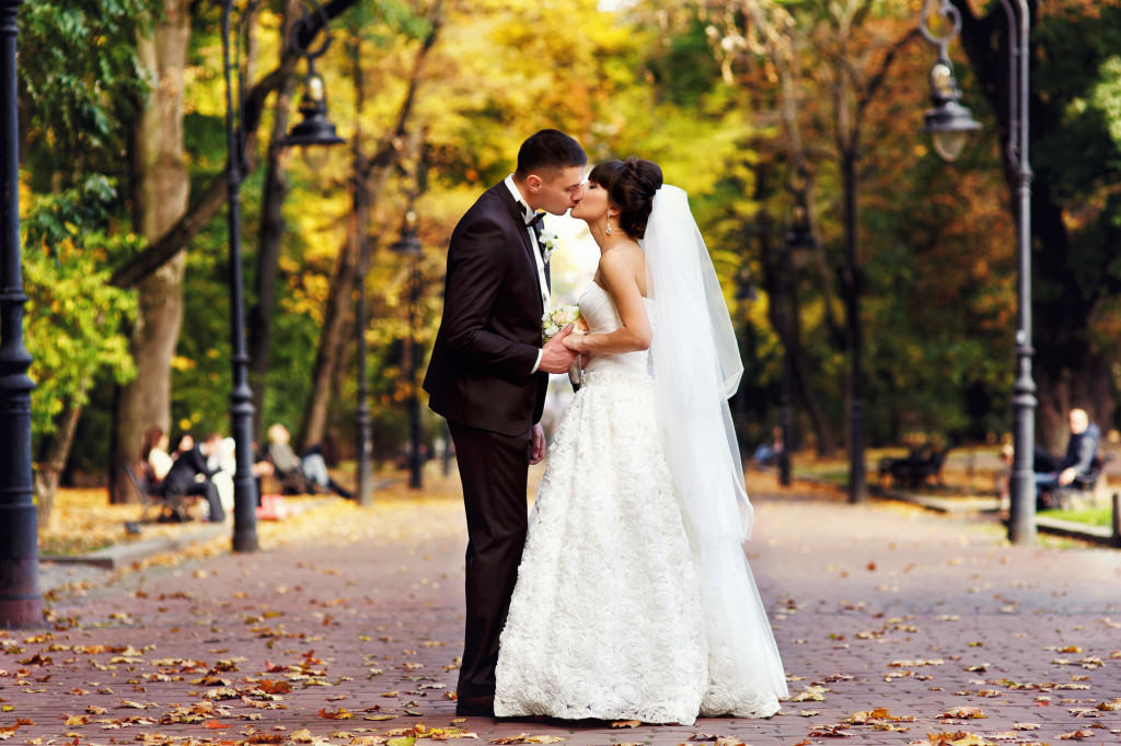 wedding couple standing in autumn park alley
