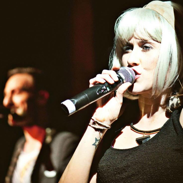 Female performer singing alongside male vocalist.