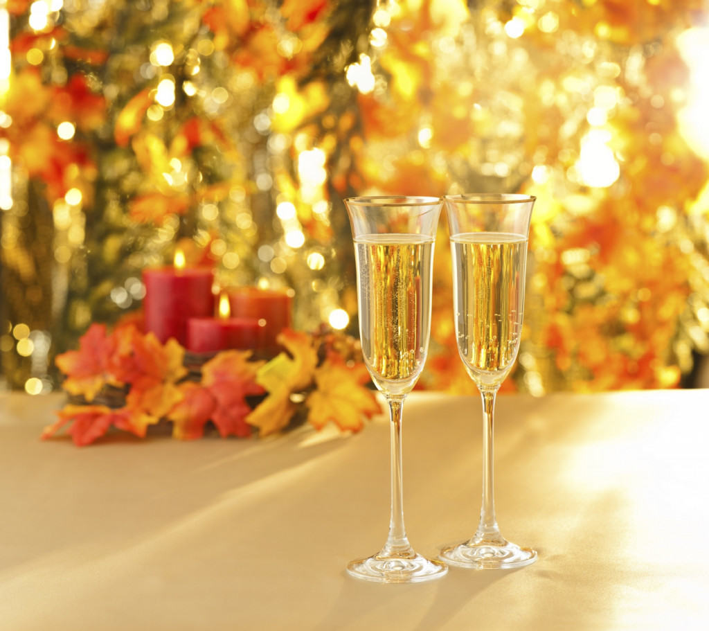 Champagne glasses for reception in front of autumn background and candles
